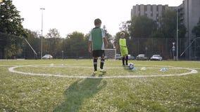 2 мальчика пиная футбольный мяч во время тренировки футбола видеоматериал