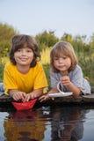 2 мальчика позволили бумажным шлюпкам от пристани реки Стоковые Фото
