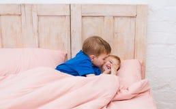 2 мальчика усмехаясь под одеялом Братья целуя и играя Стоковое Изображение RF