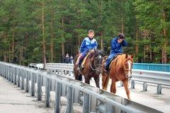 2 мальчика Buryat едут лошади на мосте в Arshan Россия Стоковое Фото