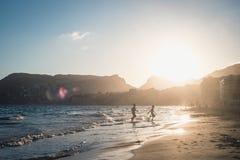 Мальчики бежать на пляже в заходе солнца Стоковые Фотографии RF