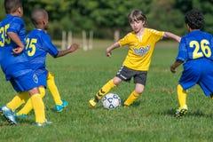 Мальчики в 2 командах играя игру футбола стоковая фотография