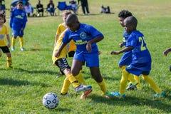 Мальчики в 2 командах играя игру футбола стоковое изображение rf