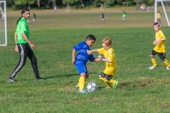 Мальчики в 2 командах играя игру футбола стоковое изображение
