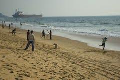 Мальчики играют сверчка на Индийском океане на пляже Candolim Индия, Goa - 27-ое января 2009 стоковое изображение