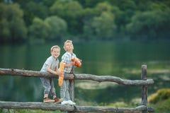 Мальчики играя в банках пруда стоковое фото