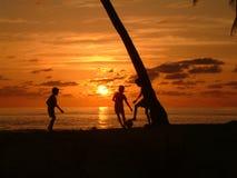 мальчики играя заход солнца Стоковая Фотография RF