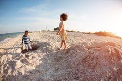 Мальчики играя с песком на пляже Стоковая Фотография RF
