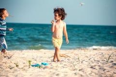 Мальчики играя с песком на пляже Стоковое фото RF