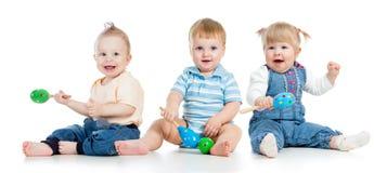 Мальчики и девушка младенцев играя с музыкальными игрушками стоковые фото