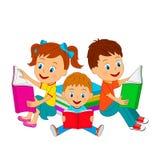 Мальчики и девушка сидят и книги чтения Стоковое фото RF