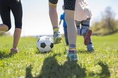 Мальчики и девушки бежать к футболу Стоковые Изображения RF