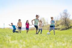 Мальчики и девушки бежать к футболу Стоковые Фотографии RF
