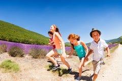 Мальчики и девушки бежать совместно в поле лаванды Стоковые Фотографии RF