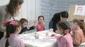 Мальчики и девушки детей сидя совместно вокруг таблицы в классе и рисовать С ими их детеныш и видеоматериал