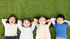 Мальчики и девушки лежа на зеленой траве Стоковая Фотография