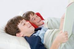 мальчики кровати читая рассказ Стоковая Фотография