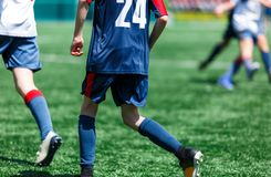Мальчики на голубом белом беге sportswear, капле, нападении на футбольное поле Молодые футболисты с шариком на зеленой траве r стоковые фото