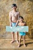 Мальчики поливая на бассейне стоковые изображения