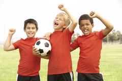 мальчики празднуя детенышей футбольной команды Стоковое Изображение