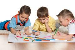 Мальчики рисуя на бумаге стоковое изображение