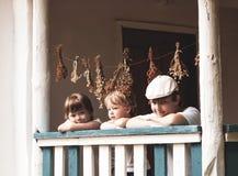 Мальчики счастливые на крылечке старого дома стоковые фотографии rf