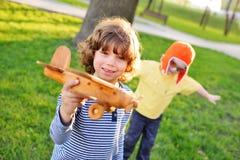 Мальчики с вьющиеся волосы играют деревянный самолет игрушки в парке Стоковая Фотография