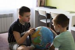 Мальчики с глобусом думают где пойти на каникулы стоковые изображения rf