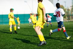 Мальчики футбольных команд в желтом белом футболе игры sportswear на зеленом поле Капая навыки Игра команды, тренировка стоковая фотография rf