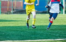 Мальчики футбольных команд в желтом белом футболе игры sportswear на зеленом поле Капая навыки Игра команды, тренировка, стоковые изображения rf