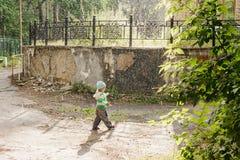 Мальчик бежать в дожде в парке стоковое изображение rf