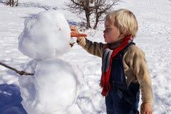 Мальчик, белокурые волосы, играя в зиме с снегом, строит снеговик Нося джинсы и шарф Стоковая Фотография RF