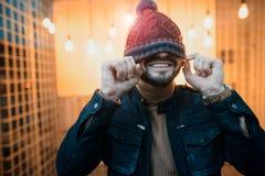Мальчик битника усмехаясь с шляпой над его наблюдает на фоне ламп Стоковые Фото