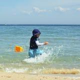 мальчик брызгая воду стоковое фото