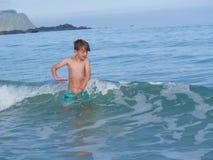 Мальчик брызгая в холодном норвежском море Стоковые Фотографии RF