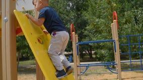 Мальчик взбирается вверх взбираясь стена на спортивной площадке летом сток-видео