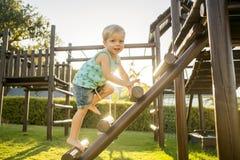Мальчик взбирается спортзал джунглей в солнечном зеленом парке стоковая фотография
