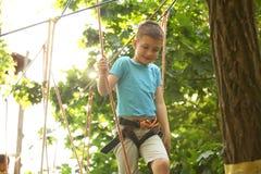 Мальчик взбираясь в парке приключения стоковые фото