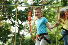 Мальчик взбираясь в парке приключения стоковое изображение