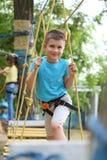 Мальчик взбираясь в парке приключения стоковое фото rf