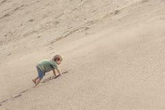 Мальчик взбираясь на песчанной дюне E стоковые фотографии rf