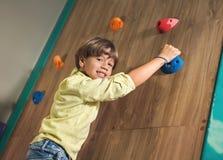 Мальчик взбираясь стена утеса крытая Стоковое фото RF