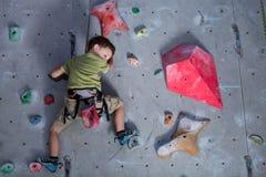 Мальчик взбираясь стена утеса крытая Стоковая Фотография