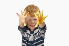 мальчик вручает его покрашенный показ Стоковое Изображение