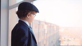 Мальчик выглядя как бизнесмен наблюдает на окне акции видеоматериалы