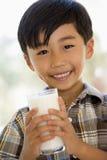 мальчик выпивая внутри помещения детенышей молока ся Стоковые Фото