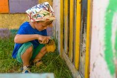 Мальчик выполняет лето краски работ картины outdoors Парень в PA Стоковое фото RF