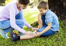 Мальчик выскоблил его ногу пока играющ стоковые фото
