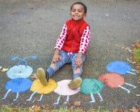 Мальчик вытягивая вверх по брюкам стоковое фото rf