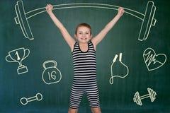 Мальчик в винтажном костюме спортсмена выполнить тренировки прочности для того чтобы поднять гантели стоковое изображение